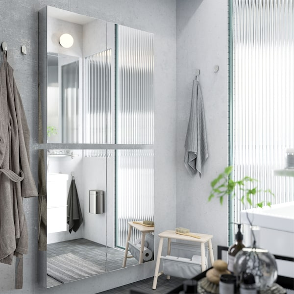 Two mirror cabinets are mounted vertically on a grey bathroom wall to create a full body mirror.