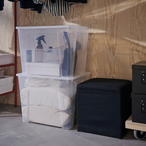 Two SAMLA transparent storage boxes are stacked on the floor, next to them is a black footstool with storage inside.