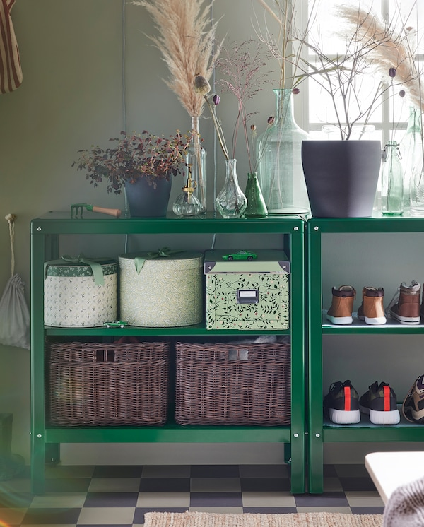 Two shelving units with decorative items on their top shelves and boxes, shoes and baskets in rattan on their lower shelves.