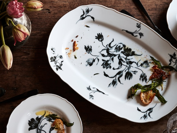 UPPLAGA serving plate and side plate with a rustic floral pattern on white placed on a wooden table with tulips.