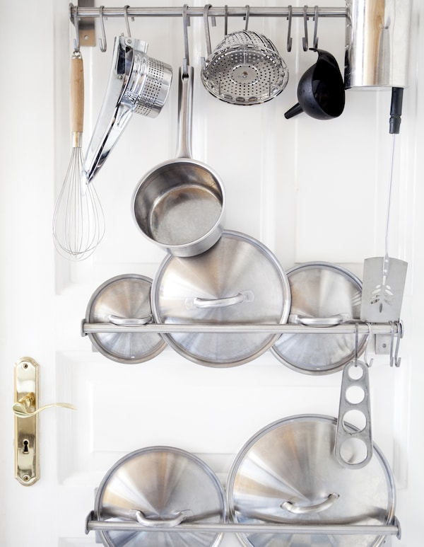 Utensils and pan lids stored on rails on a door.