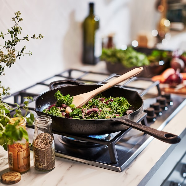 Vegetables are being fried in a VARDAGEN frying pan. It's made from cast iron: a material that distributes heat evenly.