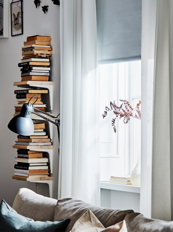 Vertical book storage made from four SIBBHULT brackets and shelves beside a window with white see-through curtains.