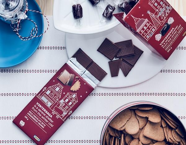 VINTERSAGA 牛奶巧克力放在叶子形状的 VINTERFEST 温特菲斯 盘子里,心形饼干放在罐子里。