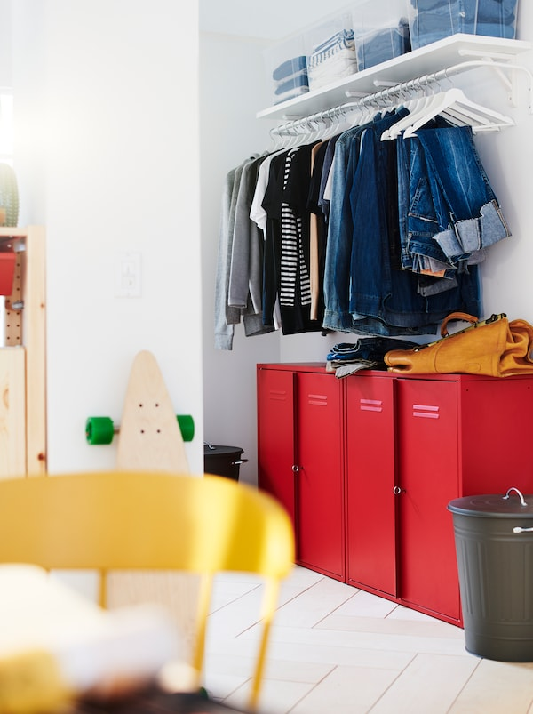 Wall section with combined wardrobe and hallway storage: red IVAR cabinets under a row of clothes on hangers on a rod.