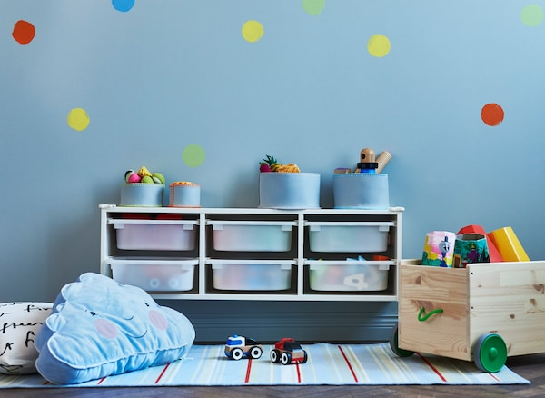Wall storage placed above a changing table during infant years can be moved down to floor level later for toy storage