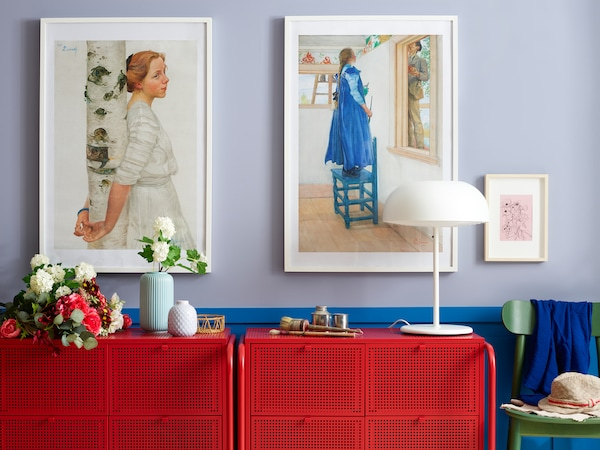 Wall with picture frames and some storage in red with a lamp, plants and a STILREN vase with a flower.