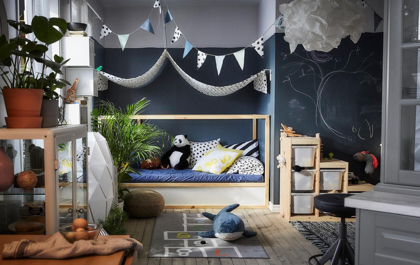 玩乐区内,放着毛绒玩具、带图案地毯和储物盒,坐卧两用床上方挂着布艺凉篷。