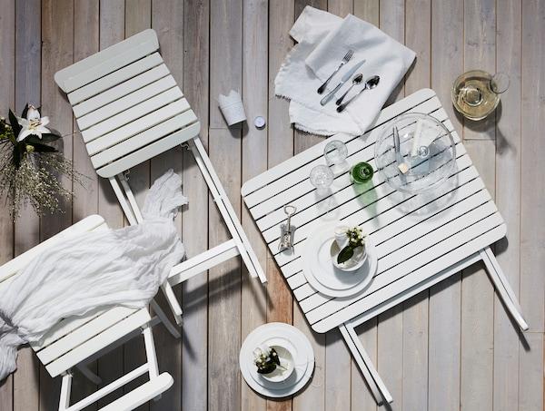 晚餐用具整齐地摆放在地板上,其中包括坚固优雅的白色餐具,搭配白色纺织品。