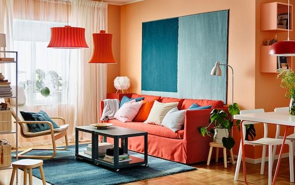 为现代风格客厅增添一抹色彩。靠着橙色的墙壁摆放 BRÅTHULT 布拉哈 Vissle 威索尔 红色/橙色三人沙发,铺上 SÖNDERÖD 桑德罗 蓝色地毯。