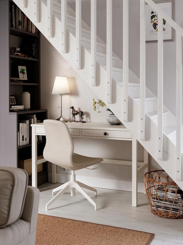 位于楼梯下方的一个工作区,由白色HEMNES 汉尼斯 书桌、LÅNGFJÄLL 隆菲尔 椅子、台灯和高高的书架组成。