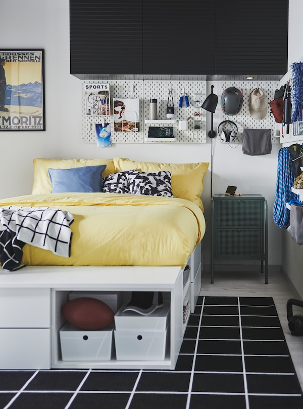 White PLATSA bed in a room where climbing equipment and youthful accessories are arranged on SKÅDIS pegboards on the walls.