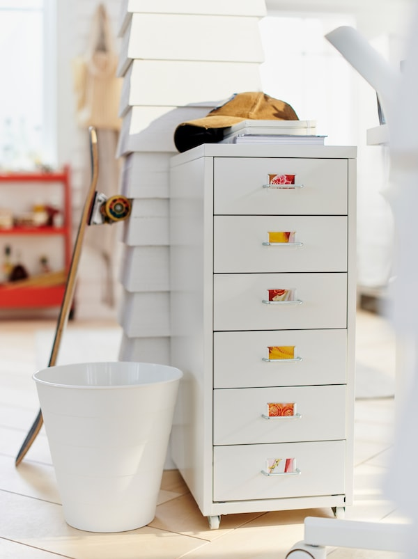 White room where a light HELMER drawer unit with colourful labels stands by a wooden post with a skateboard leaning on it.