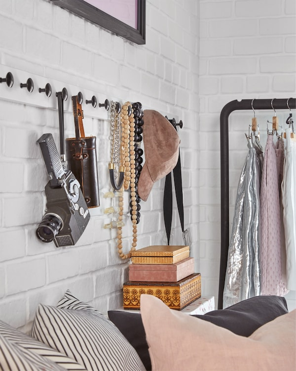 White stained/anthracite racks with knobs are mounted on a wall and accessories hang on the knobs.