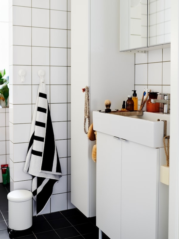 White-tiled bathroom furnished with white LILLÅNGEN cabinets and washbasin, and dotted with decorations and accessories.