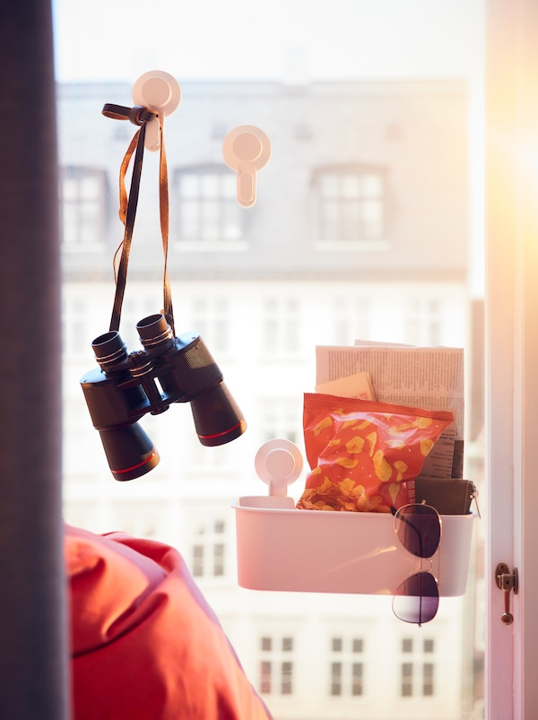 Window overlooking multistorey facades. TISKEN suction-cup hooks and basket on the glass hold binoculars and snacks.