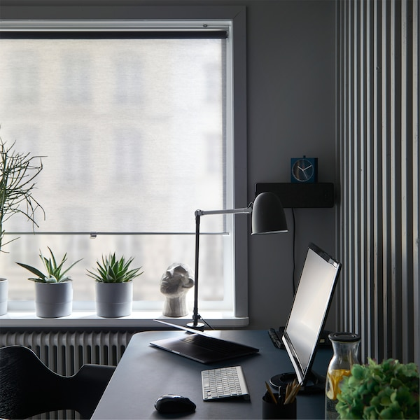Windows in a home office with SKOGSKLÖVER grey roller blind drawn almost down, behind a desk with a lamp and computer screen.