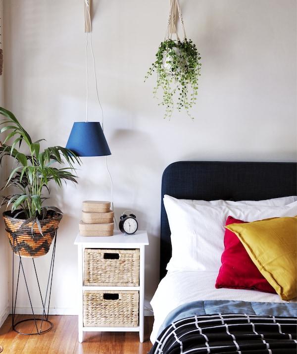 卧室的床上堆放着彩色的靠垫,旁边放置着床边桌和植物。