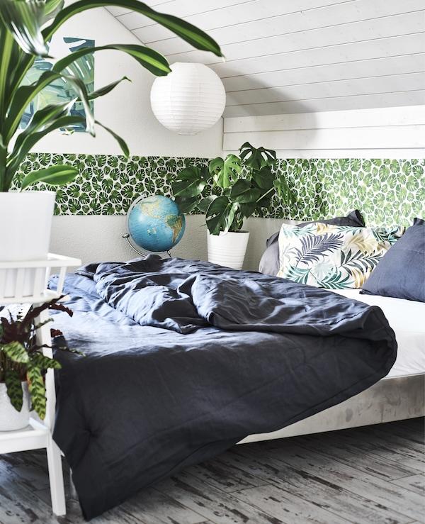 卧室里放着盆栽植物、绿叶图案的饰边和深色床上用品。