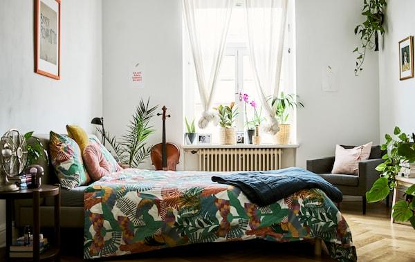 卧室里放着许多植物,窗户上挂着纱帘,地上铺着镶木地板,床上铺着印有热带图案的被子。