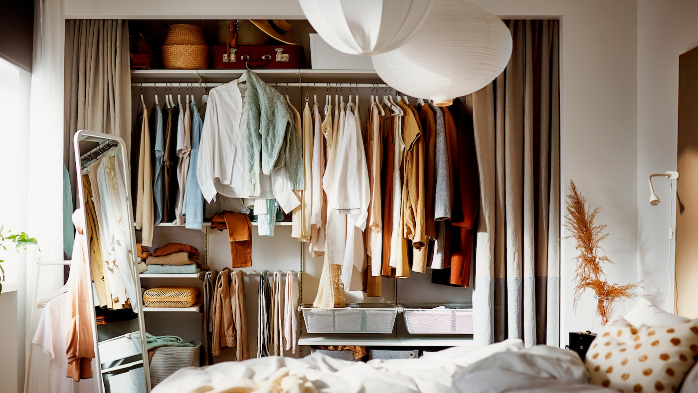 卧室里一个全墙宽的凹室,挂帘拉开,露出其中利用BOAXEL 博阿克塞 储物组合打造的衣柜。