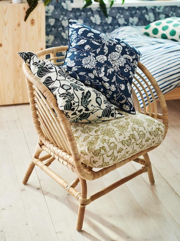 卧室里有一张藤制椅子,上面有三个颜色各异的靠垫,每个靠垫的花纹图案略有差异。