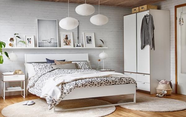 卧室内为白色砖墙和木质地板,里面放着一张白色/浅灰色双人床。