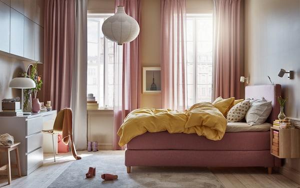 卧室配浅棕粉色的沙发床,黄色被套和枕套,白色灯具和白色梳妆台。