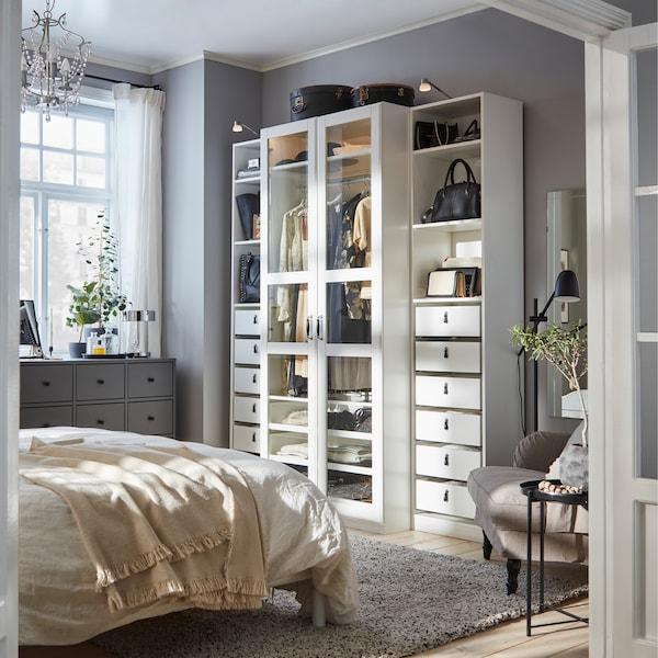 卧室配有带玻璃门的白色衣柜、深灰色抽屉柜和米灰色扶手椅。