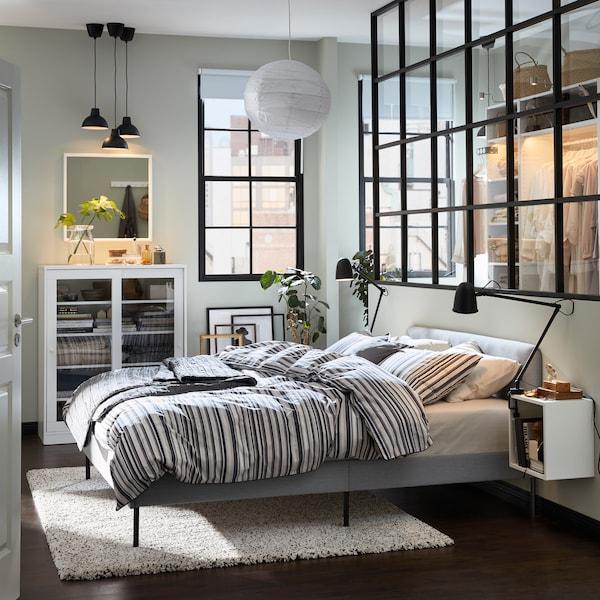 卧室配有灰色软垫床架、灰色地毯、白色玻璃门柜和黑色灯具。