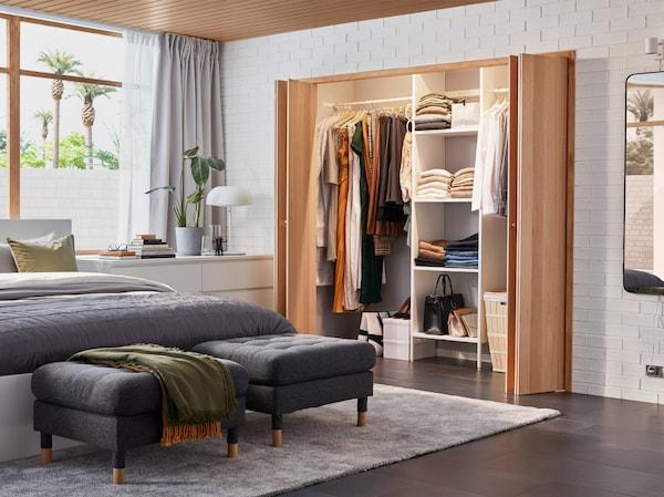 卧室配有内置衣柜解决方案、白色床架、白色抽屉柜和两把深灰色脚凳。