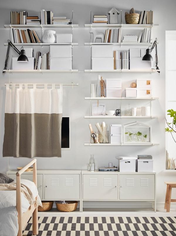 卧室墙壁上,白色的BERGSHULT 贝利斯胡特/PERSHULT 伯舒特 搁板上,摆满储物盒和装饰品;还有一个沿墙旋转的白色IKEA PS 柜子。