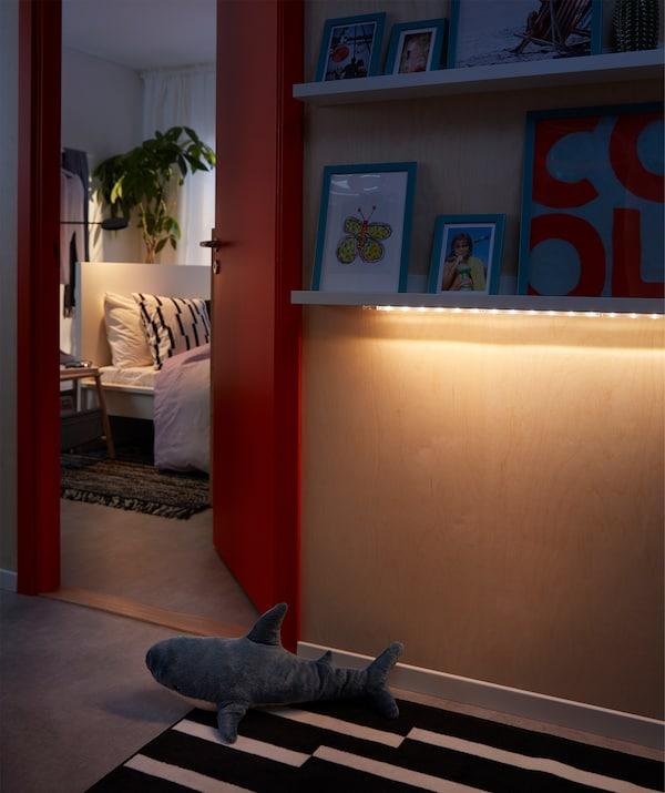 卧室外的空间里,壁式图片架下方的LED照明条散发出柔和的光,照亮了地板。