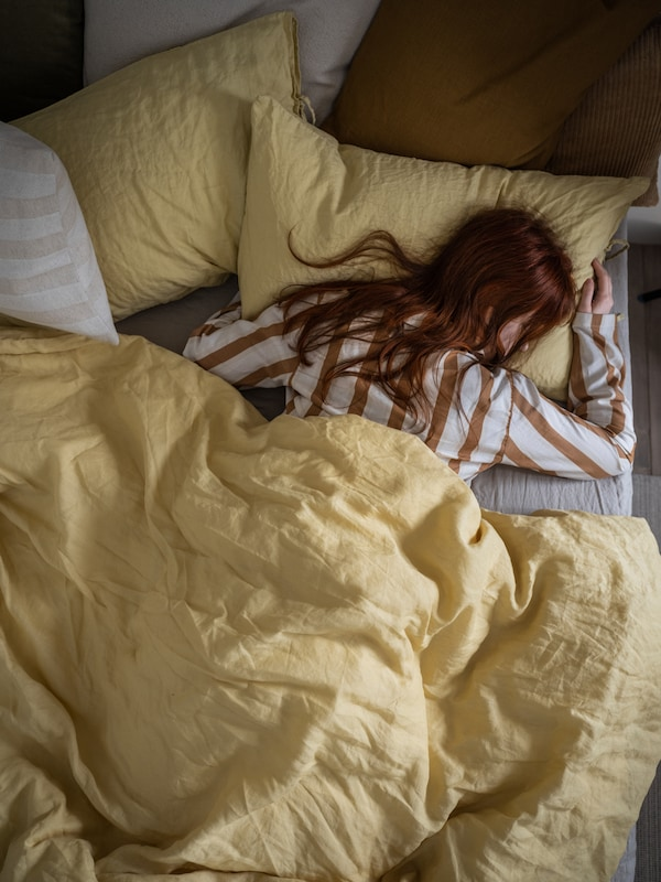 Woman in striped pyjamas sleeping soundly in a bed made with light-yellow PUDERVIVA pillowcases and quilt cover.