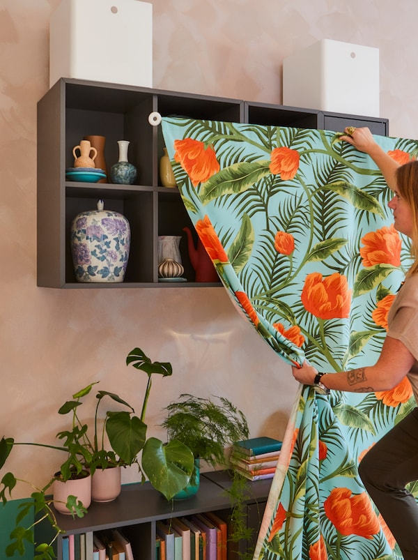 Woman on her way to cover high and low sections of wall-mounted shelves with SOMMAR 2020 fabric set on an IRJA curtain rod.