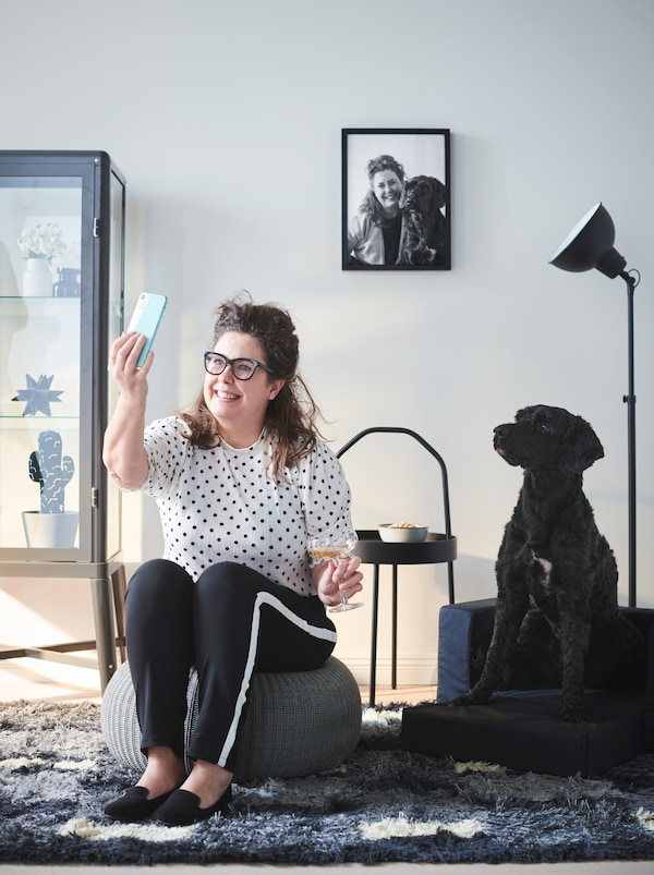 Woman sitting in a living room on a SANDARED pouffe, snapping a selfie of herself and her black dog sitting next to her.