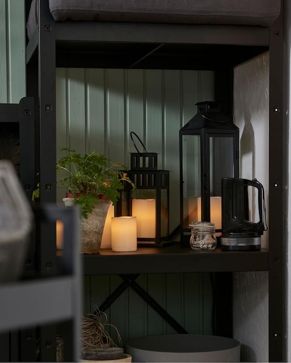 屋内转角处放着一个搁架单元,它的中间一层上摆放着各种LED蜡烛和一株植物,占据了一半的空间。