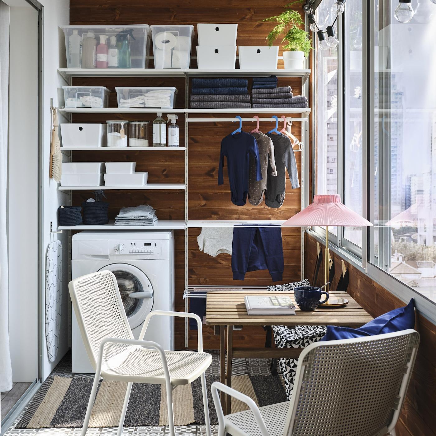 狭小的阳台上摆放着一系列白色洗衣储物家具、洗衣机、小型户外用桌和两把白色/米色椅子。