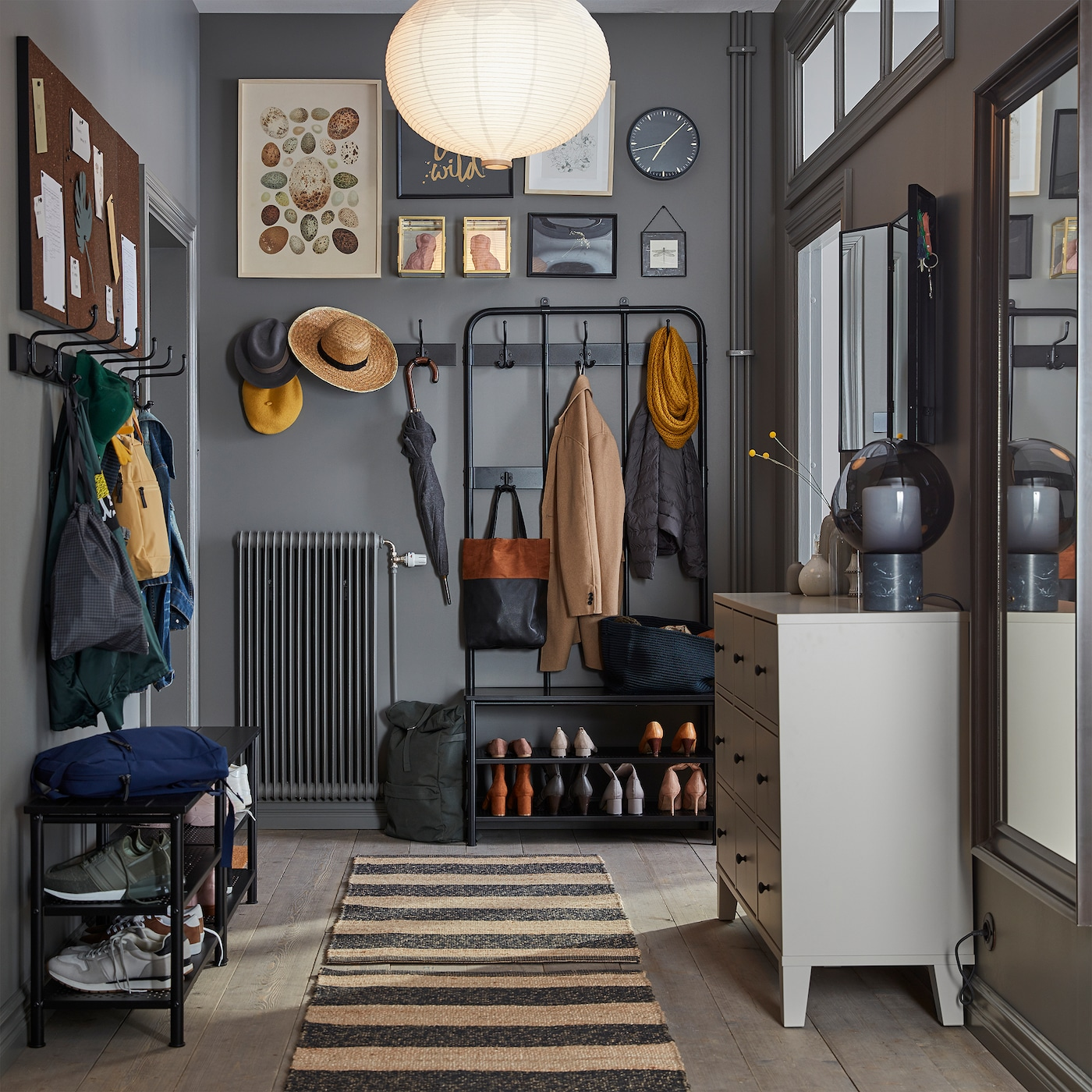 狭窄的灰色门厅配有条纹地毯,米色抽屉柜、全身镜和可放鞋的长凳。