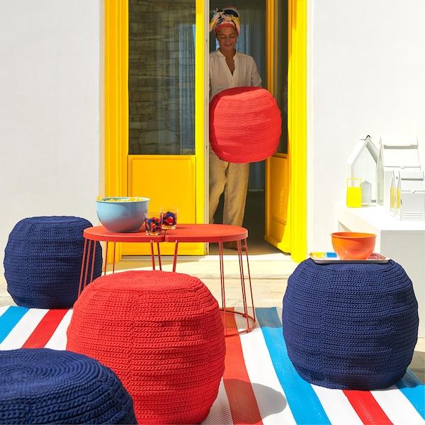 夏日的户外空间里摆放着桌子和饰有钩织垫套的 OTTERÖN/INNERSKÄR 欧特洛/因那晒尔 矮凳。