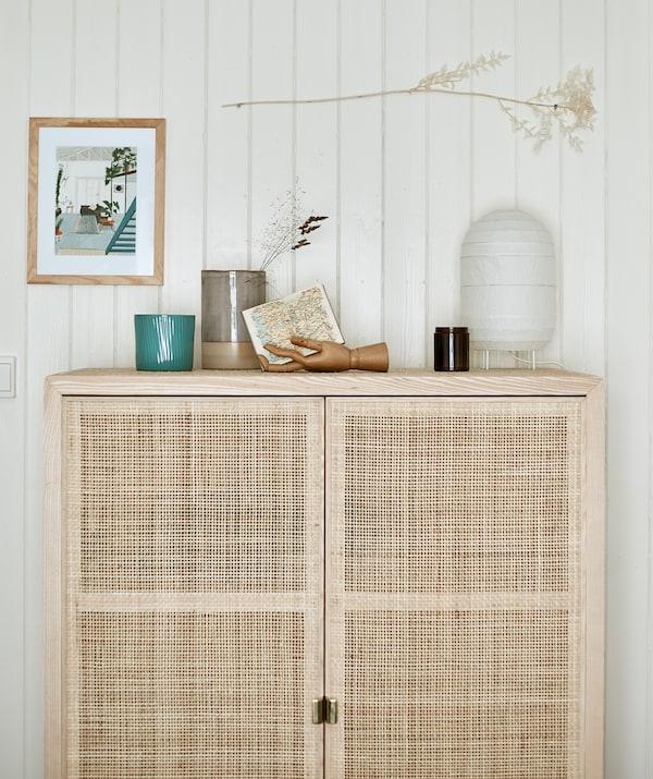 镶板墙前放着较高的带木门木材储物柜,顶部展示着纸灯笼和其他物品。