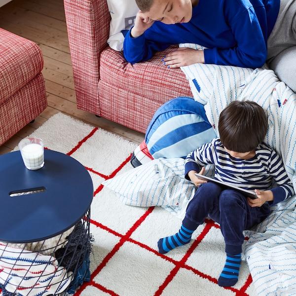 小男孩手里拿着平板电脑,坐在从沙发垂落的被子的一角。长辈在沙发上看着。