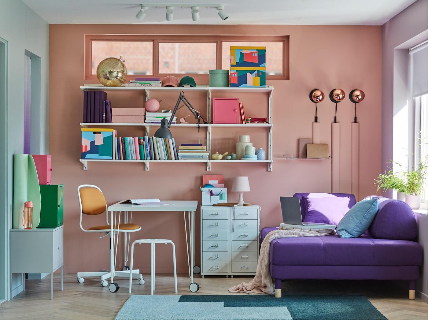 小型家庭办公室配有白色 LINNMON 利蒙/KRILLE 克瑞尔 带脚轮桌子、一些搁板、储物柜和沙发床。