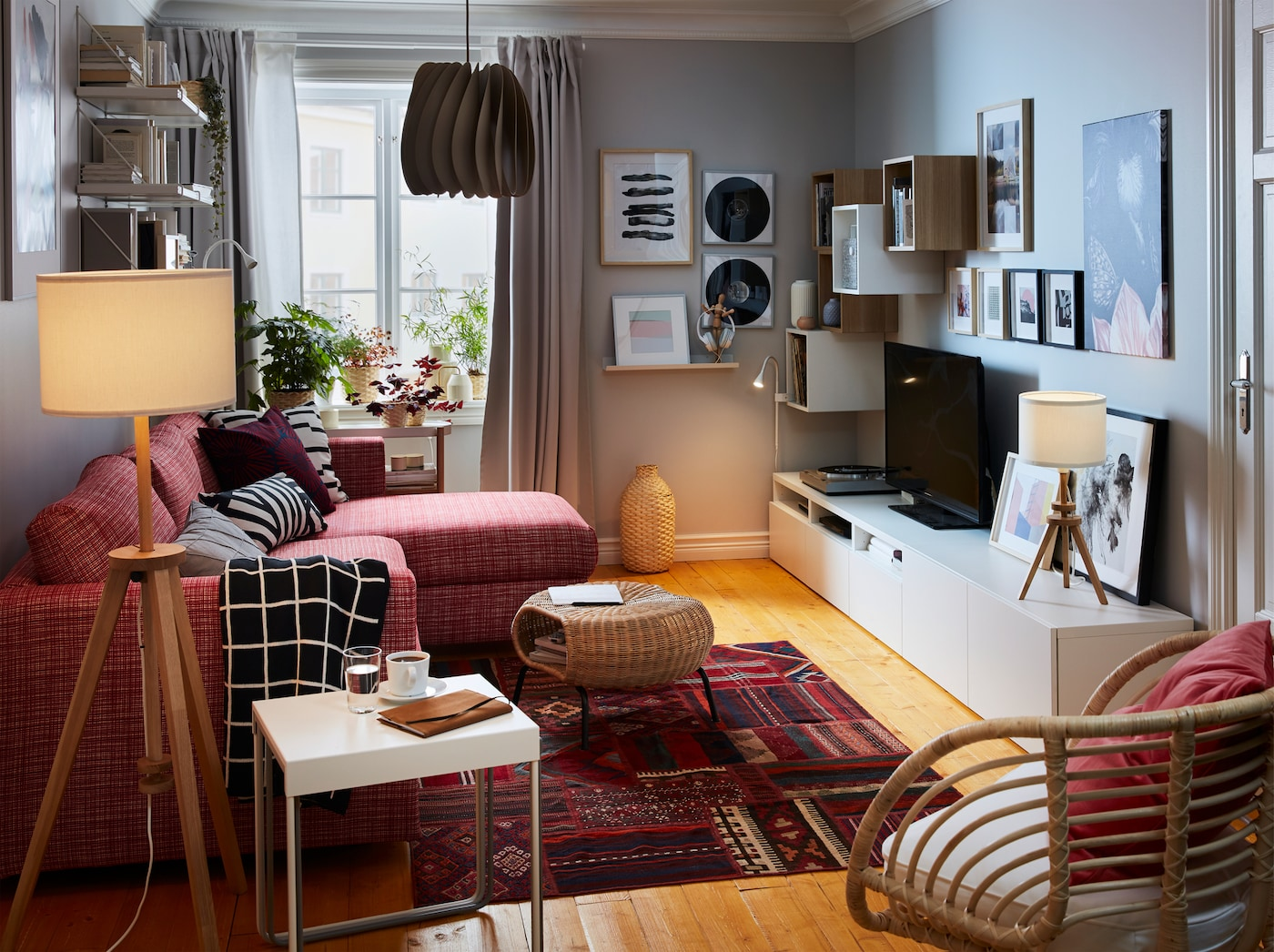 小型客厅配有红色波斯图案地毯、红色沙发、灰色窗帘、藤制扶手椅和情调照明。