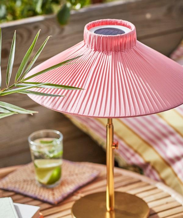小桌子上放着一盏洒满阳光的 SOLVINDEN 索文顿 太阳能台灯和盛有饮料和青柠块的杯子。