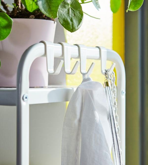 需要新颖的小卧室储物创意?利用开放式搁架单元,侧面带有精巧的挂钩,可悬挂居家服!
