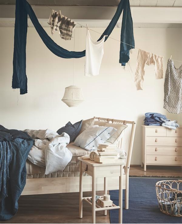 亚麻布悬挂在木质床架、床边桌和抽屉柜上。