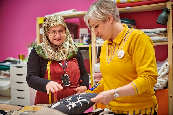Yalla Trappan是一项社会项目,其内容是在瑞典的宜家马尔默商场提供缝纫服务。Neire Kerimovska和Karin Wingren在讨论一种垫套。
