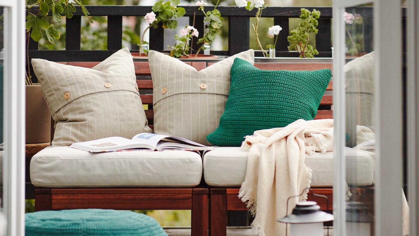 阳台上摆放着一张木制户外沙发,沙发上有白色和绿色的靠垫、一条休闲毯和一本打开的书,沙发后是一些绿植。