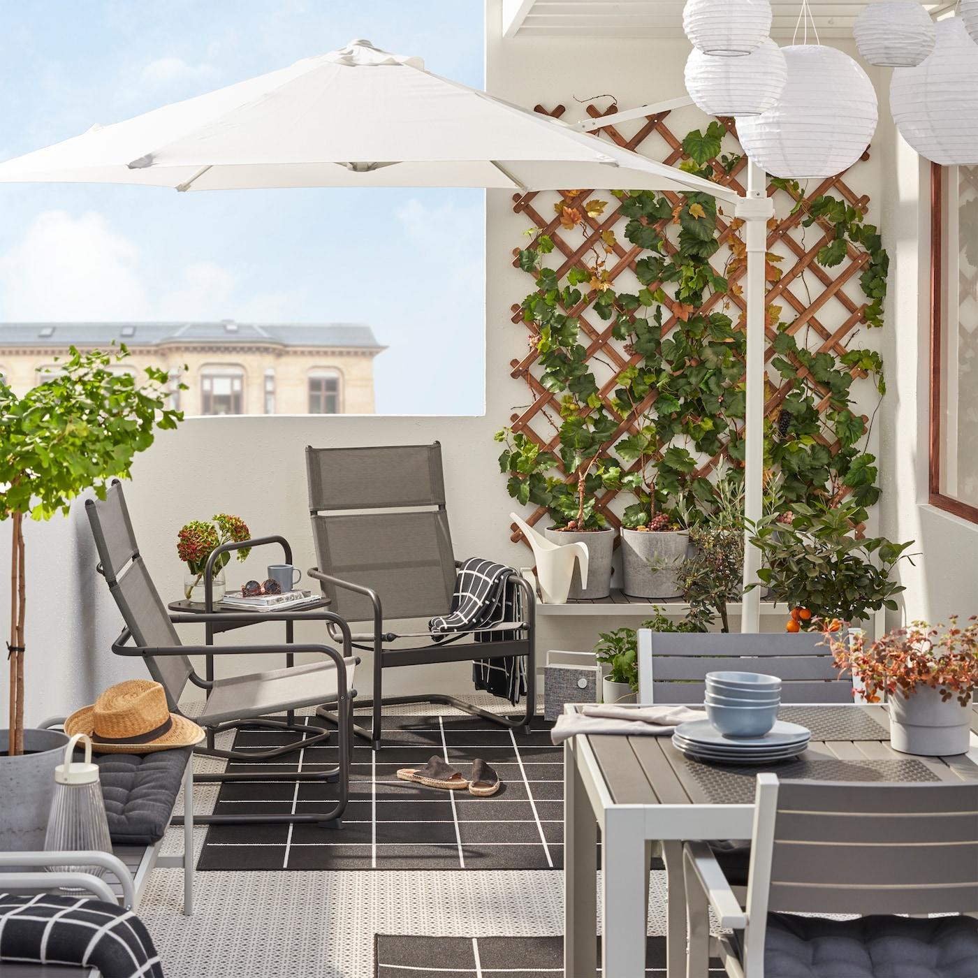 阳台上边放着 HUSARÖ 胡萨罗 扶手椅和边桌、白色阳伞、灰色餐桌和椅子,以及黑色/白色地毯。